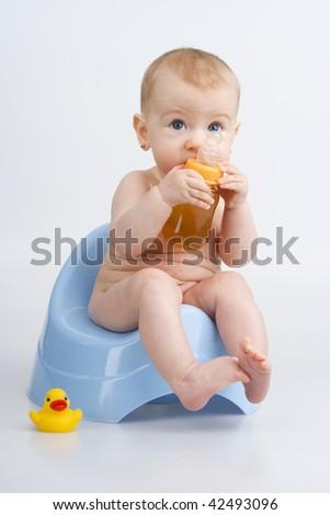 Child on potty with bottle teas and quack - quack,on white background. - stock photo