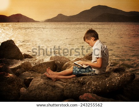Child on the beach with tablet computer, filtered - stock photo