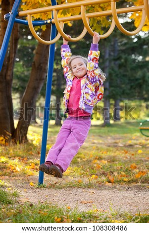 Child on the playground hanging on the bar - stock photo