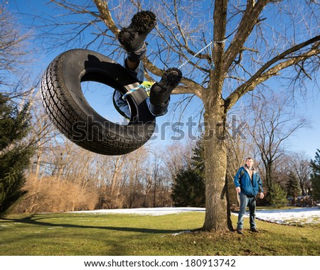 Child on Tire Swing. Wide Angle View From Below. - stock photo