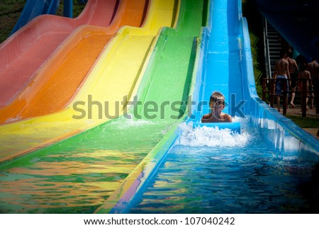 Child on water slide at aquapark - stock photo