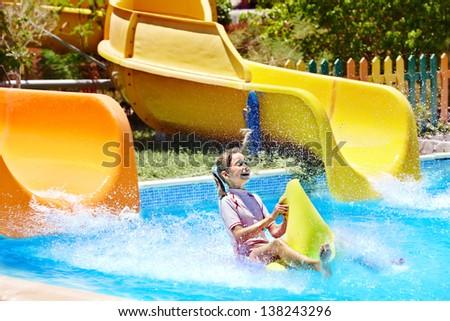 Child on water slide at aquapark. Summer holiday.. - stock photo