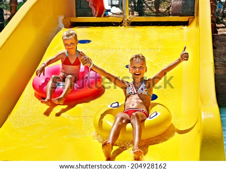 Child on water slide at aquapark. Summer holiday. - stock photo