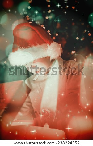 Child opening his christmas present against candle burning against festive background - stock photo