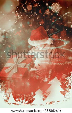 Child opening his christmas present against glittering christmas tree design - stock photo
