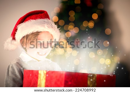 Child opening his christmas present against snow - stock photo