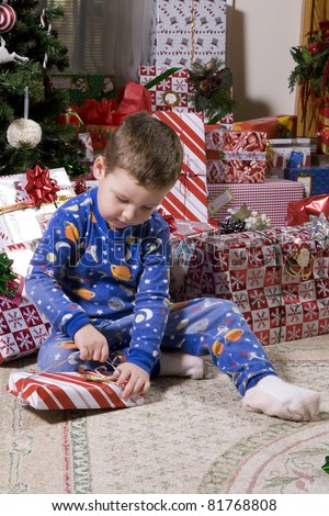 Child opening presents near the Christmas tree, Holiday has finally arrived - stock photo