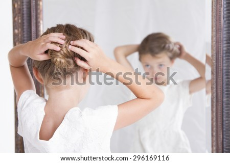 Child or young girl fixing her hair while looking in the mirror.