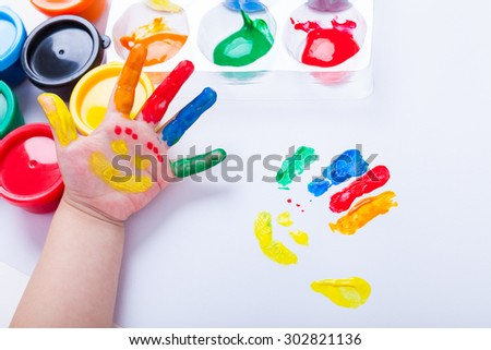 Child paint her palm with smiling face various colors using multicolored drawing tools. Studio shot - stock photo