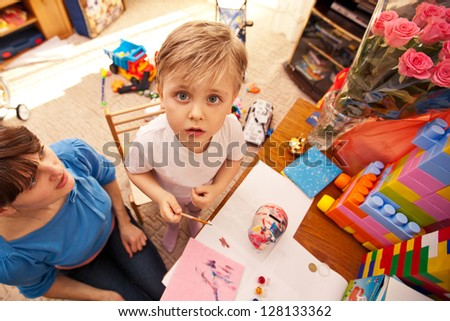 child painting in kindergarten with a teacher. little boy playing with water colors. education. - stock photo