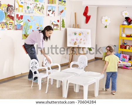 Child painting in preschool. Teacher help by little girl. - stock photo
