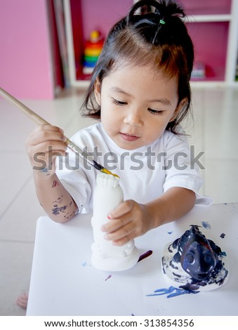 Child painting, little girl having fun to paint on stucco doll,selective focus