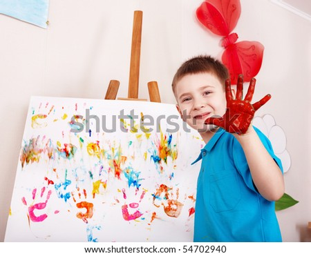 Child painting on easel by hands.  Preschool. - stock photo
