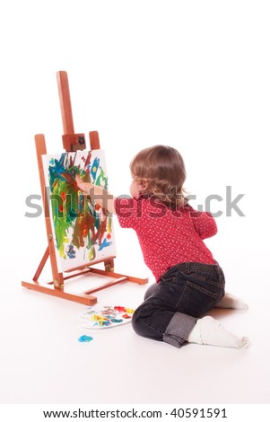 Child painting on easel with fingers - stock photo