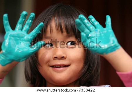 child painting with hands and playing with colours (chinese child) - stock photo