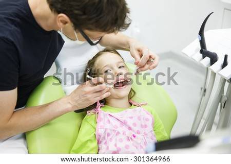 Child patient in pediatric dentists office on her regular checkup for tooth decay, caries and gum disease. Early prevention, oral hygiene and milk teeth care concept.  - stock photo