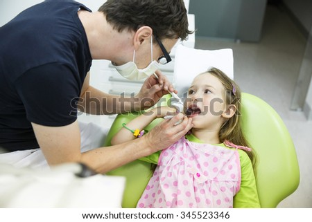 Child patient sitting in dental chair in pediatric dentists office, being examined by her dentist. Early prevention, oral hygiene and milk teeth care concept.  - stock photo
