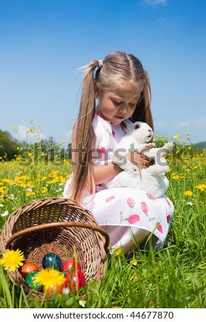 Child petting the Easter bunny on a spring meadow, eggs in a basket and lots of flowers also to be seen. It is not entirely clear whether the bunny enjoys the treatment - stock photo