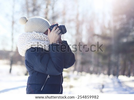 Child photographer takes picture on the digital camera outdoors in winter sunny day - stock photo