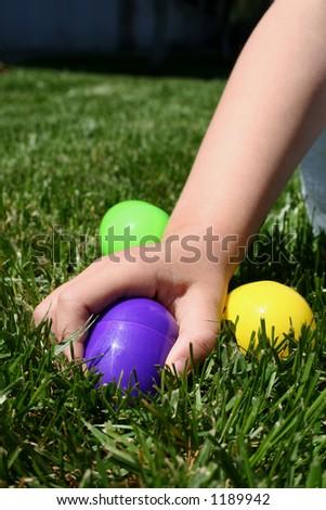Child picking up easter egg - stock photo