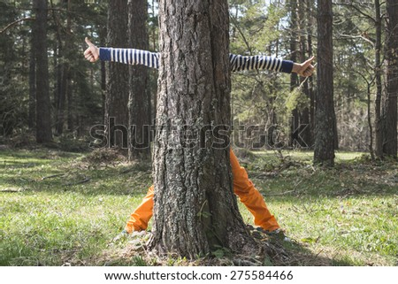 Child play in the forest hidden behind a tree - stock photo