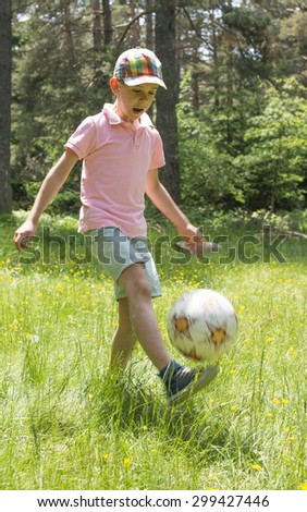 Child play with a ball in the mountain. Green grass - stock photo