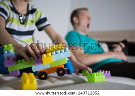 Child playing alone and his father yawning - stock photo