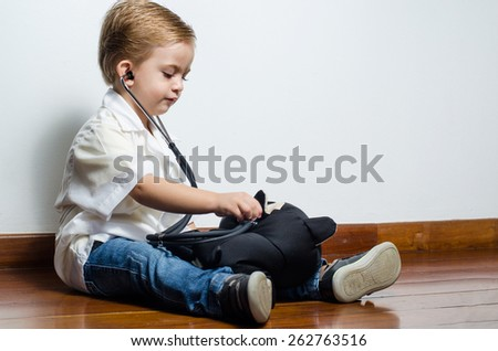 Child playing at being doctor stuffed cat - stock photo