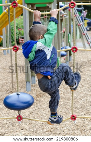 Child playing at children playground, climbing the  rope ladder. - stock photo