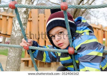 Child playing at children playground, climbing the  rope ladder frame. - stock photo