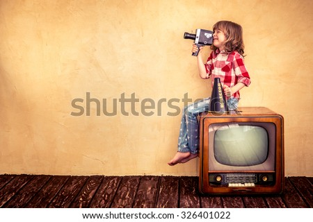 Child playing at home. Kid making a film with retro camera. Cinema concept