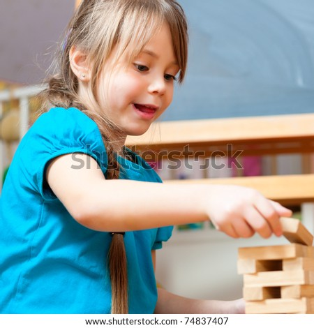 child playing at home with bricks in the nursery - stock photo