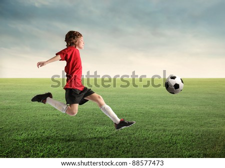 Child playing football on a meadow - stock photo
