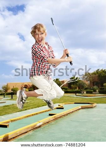 Child playing golf. - stock photo