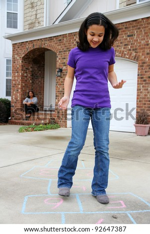 Child playing hopscotch outside at her home