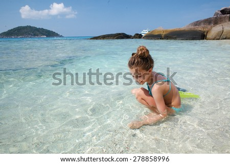 Child playing in clear sea water on a tropical beach - stock photo