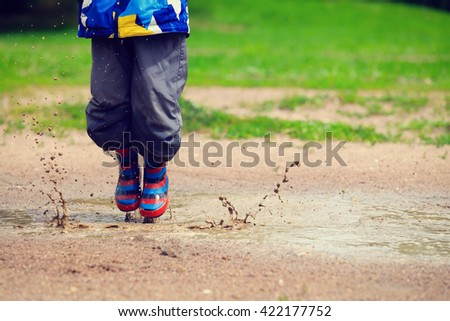 child playing in muddy puddle