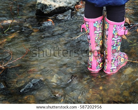 Child playing in river. Pink wellington boots.
