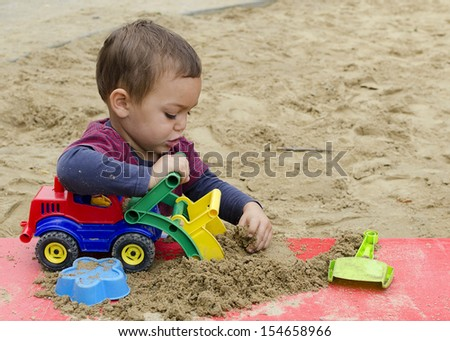 Child playing in sandpit with toy truck car or digger. - stock photo