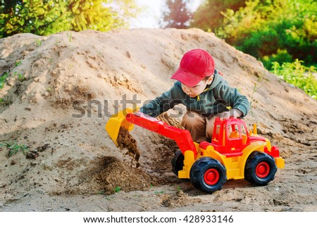 child playing in the sand excavator - stock photo