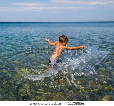 Child playing in the waves - stock photo
