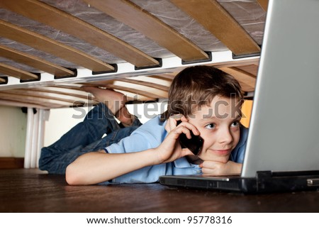 Child playing laptop under the bed. Computer Addiction - stock photo