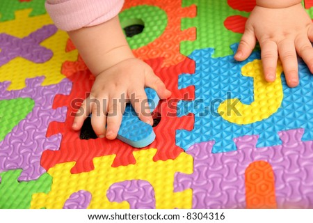 child playing multi colored alphabet puzzle - stock photo
