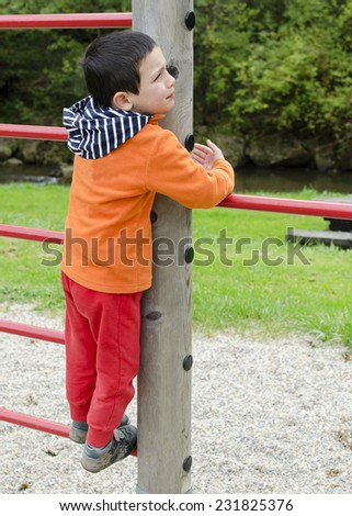 Child playing on a climbing frame at children playground at park.  - stock photo