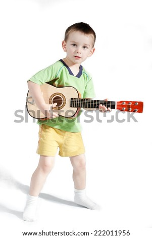 Child playing on guitar isolated on a white background - stock photo