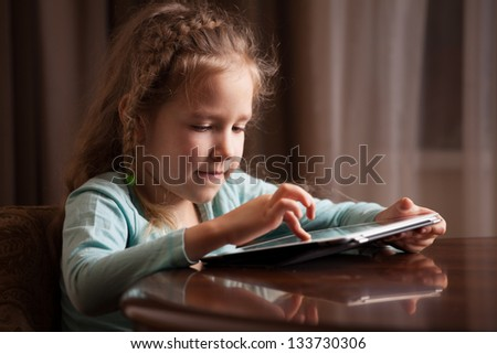 Child playing on tablet pc. Girl looking at computer