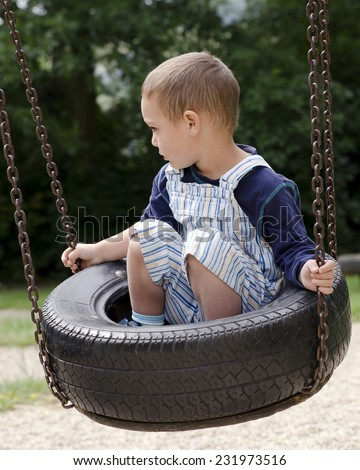 Child playing on tire swing at children  playground park. - stock photo