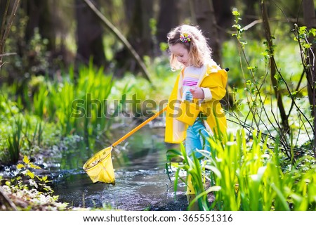 Child playing outdoors. Preschooler kid catching frog with colorful net. Little girl fishing  in summer. Adventure kindergarten day trip into wild nature, young explorer hiking and watching animals. - stock photo