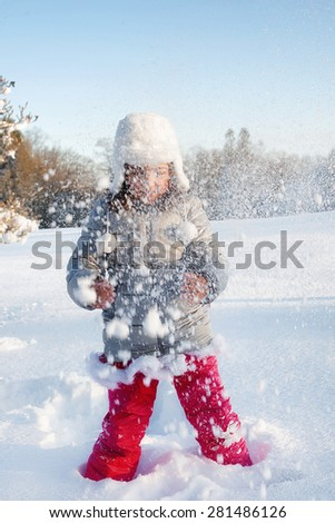 Child playing snowball fight in Winter at Christmas. - stock photo