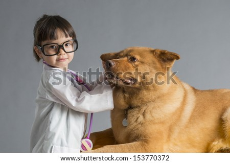 Child playing veterinarian with dog - stock photo